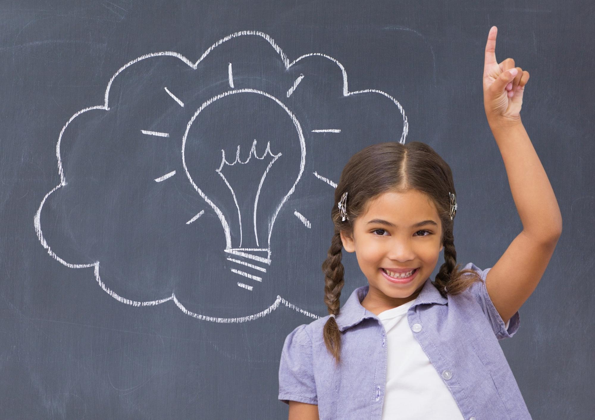 Schoolgirl raising her hand in front of a blackboard